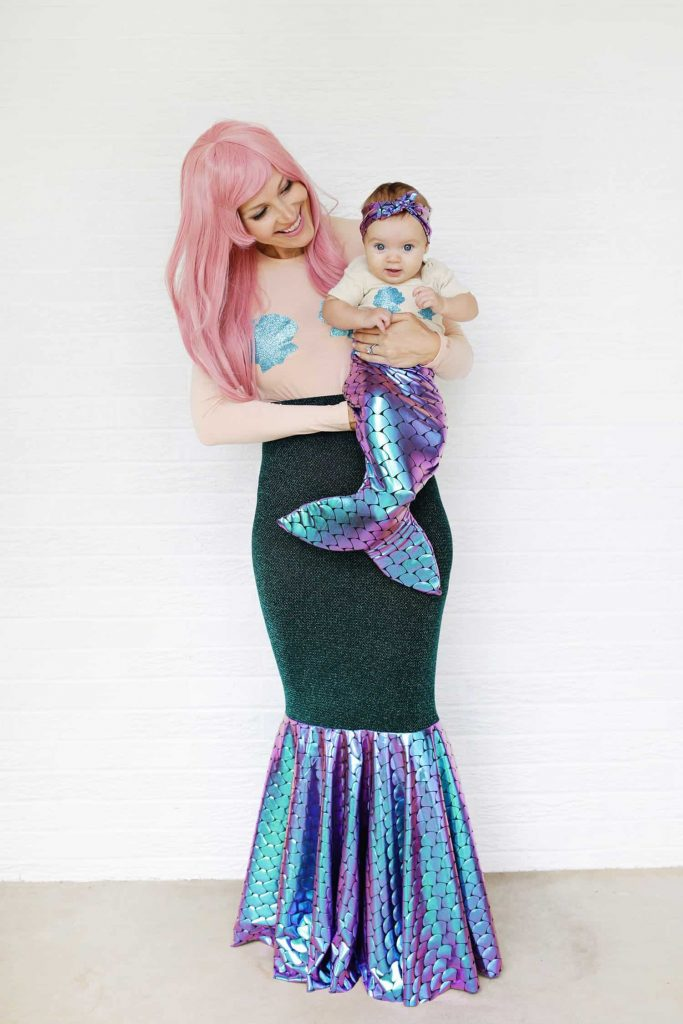 Mom holding baby daughter, both are dressed as mermaids
